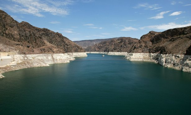 The white 'bathtub ring' on the rocks along the Colorado River is from mineral deposits left by higher levels of water. A seven year drought and increased water demand spurred by explosive population growth in the Southwest has caused the water level to drop over 100 feet to its lowest level since the 1960s.