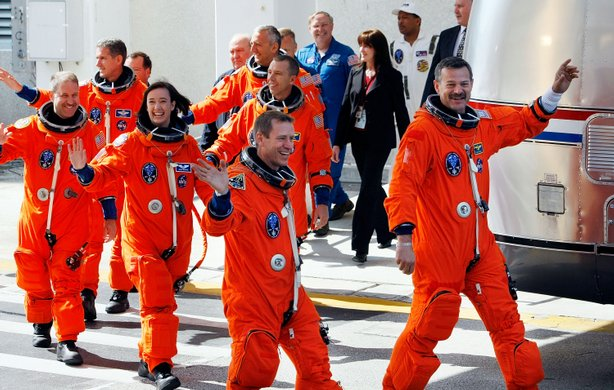 Space Shuttle Atlantis STS-125 astronauts, (R-L) commander Scott Altman, pilot Greg Johnson, mission specialists Megan McArthur, mission specialists John Grunsfeld, Mission Specialist Andrew J. Feustel, and mission specialist Michael T. Good wave as they prepare to head to the launch pad for a 2:01pm launch today at Kennedy Space Center on May 11, 2009 in Cape Canaveral, Florida.