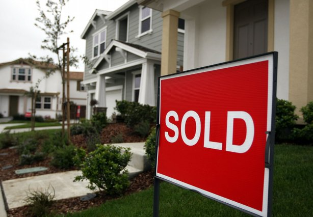 A sold sign is posted in front of a home at a new housing development.