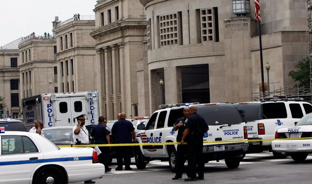Police gather in front of the Holocaust Museum following a shooting at the museum June 10, 2009 in Washington, DC. According to reports, James van Brunn, 88, walked into the Holocaust Museum and exchanged fire with security guards, shooting one before being shot himself.