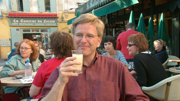 Rick Steves drinking pastis at a cafe in France.
