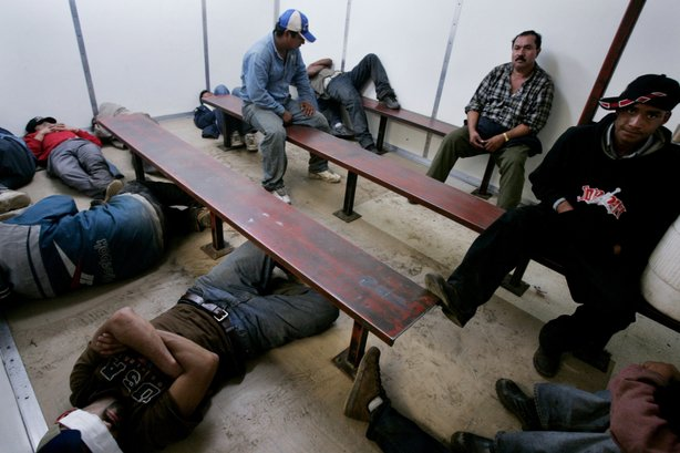 Illegal immigrants sit in a Customs and Border Patrol detention facility after being detained October 17, 2007 in Campo, California.