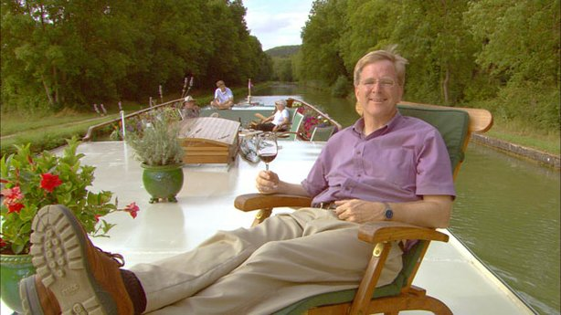 With his all-new series, Rick Steves (hard at work here cruising a canal in Burgundy) finds and shares the good life in Europe. 