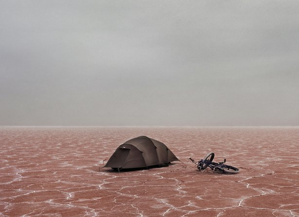 Lake Eyre and its salt flats in South Australia. In this photo you can see photographer Murray Fredericks' small tent and bike used on his solo camping trips.