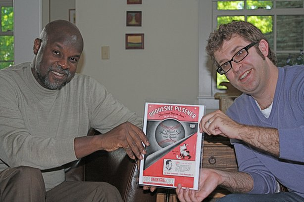 Jason Mishelow (right) asks HISTORY DETECTIVES host Tukufu Zuberi (left) to find out whether the game recorded in this Pittsburgh Pirates baseball program played a role in integrating professional baseball. In this game, Jackie Robinsons All Star team included black and white athletes, yet this game occurred six months before Robinson became Americas first black major league baseball player.