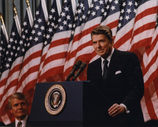 President Ronald Wilson Reagan at the podium with American flags lining the background.