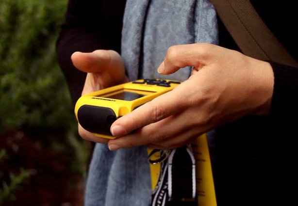 A treasure tracker uses a GPS navigation system in the adventure-filled game of geocaching.