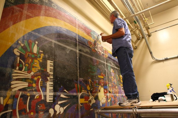 Conservator Gary Hulbert layers the mural with resin, tissue paper and fabric before he removes it from the wall. 