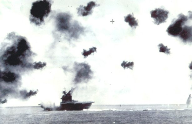 Scene taken of the actual battle in 1942 of a stricken ship in the water, surrounded by antiflak gun shots.