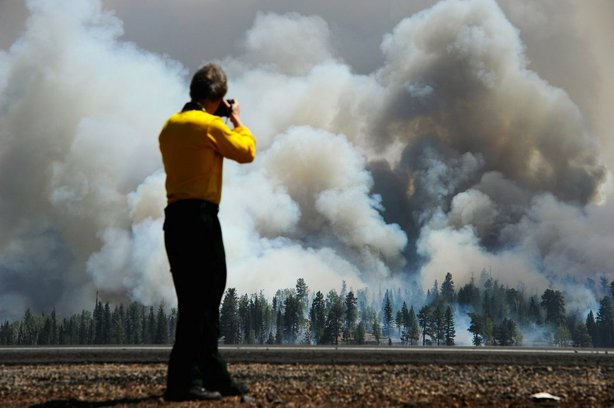 A photographer looks on as smoke rises around the Lee Valley Recreational area in the Apache National Forest on June 12, 2011 in Big Lake, Arizona.