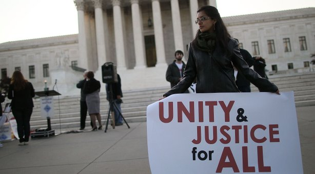 A women holds a sign that reads 'Unity & Justice for All' during a protest in front of the U.S. Supreme Court, on April 25, 2012 in Washington, DC.