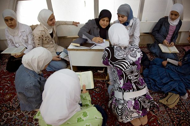 A teacher instructs her student on correct pronunciation of Qur'anic verse.