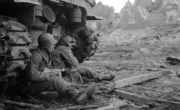 Two soldiers in Geich, Germany, pause for a cigarette behind a tank on December 11, 1944.
