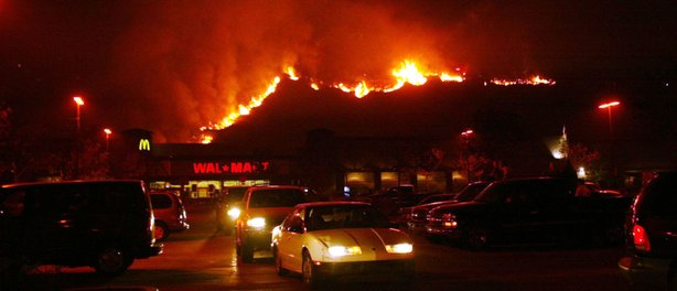 A fireline in the Cedar Fire makes its way down the hill near a Walmart October 27, 2003 near Lakeside in San Diego, California.