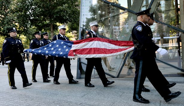 Port Authority Police Officers carry an American flag that flew over at the World Trade Center towers during memorial ceremonies for the eleventh anniversary of the terrorist attacks on lower Manhattan at the World Trade Center site September 11, 2012 in New York City.