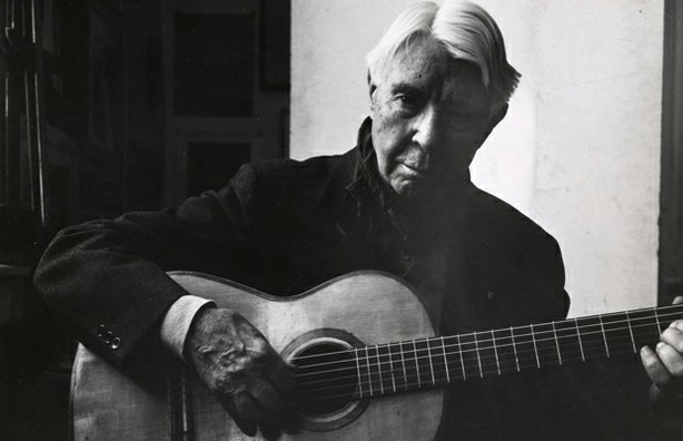 Carl Sandburg playing his guitar.