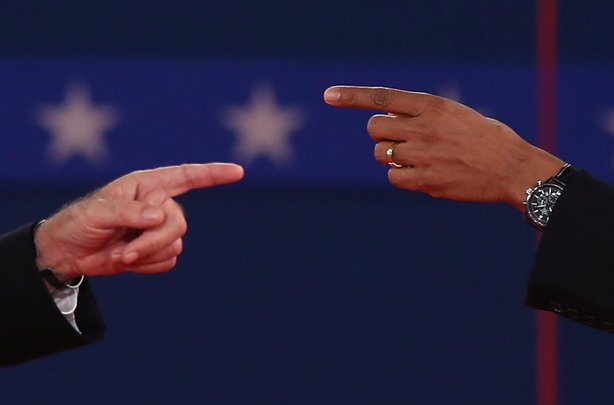Republican presidential candidate Mitt Romney (L) and U.S. President Barack Obama talk to each other during a town hall style debate at Hofstra University October 16, 2012 in Hempstead, New York. During the second of three presidential debates, the candidates fielded questions from audience members on a wide variety of issues.