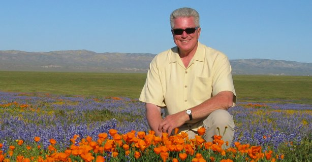 Huell Howser amongst the California poppies, wearing his iconic sunglasses and gold shirt.  