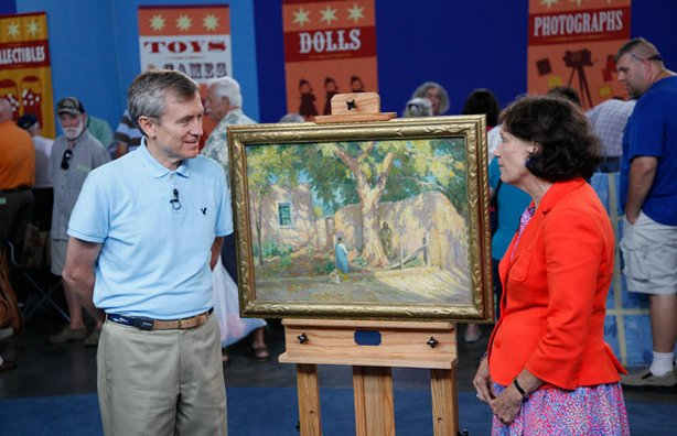 Appraiser Debra Force (right) with a guest and his Joseph Henry Sharp oil painting.