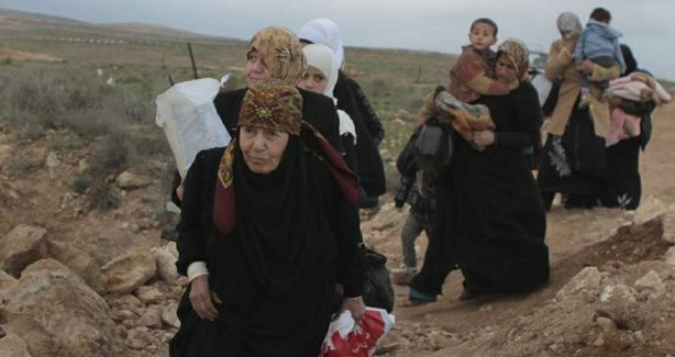 A line of Syrian refugee women, some carrying children, cross into Jordan from southern Syria. The outflow this year has been staggering. 
