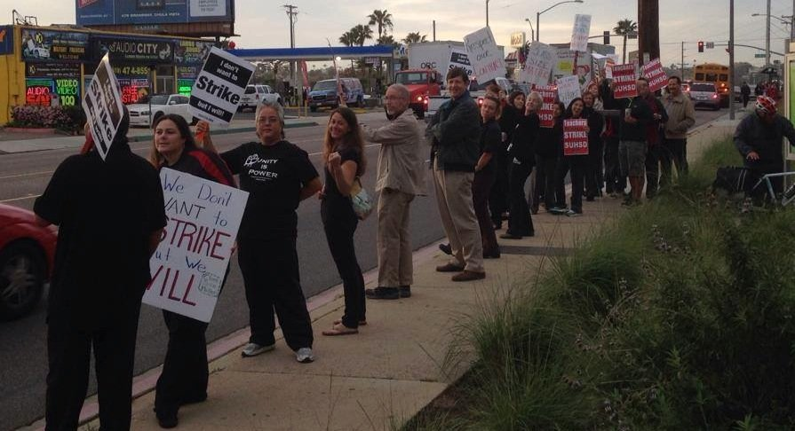 People with Sweetwater Education Association hold signs and rally in Chula Vista on March 21, 2014.