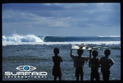 Promotional graphic for SurfAid International with children holding surfboards facing the ocean.