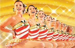 Image of the iconic high-kicking ensemble, the Rockettes, in seasonally festive costumes for their production, Radio City Christmas Spectacular.