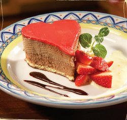 Promotional photo of Valentine's Day dessert at Sevilla Restaurant & Tapas Bar: Heart Shaped Cupidón Cake for Two/ Strawberry mousse and Chocolate ganache.