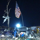 A group of U.S. Marines who were on hand in Moore, Oklahoma to help with search and rescue efforts created a scene of hope and support amid the destruction by raising an American flag found in the rubble.