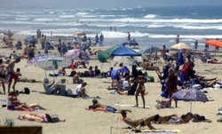 Beachgoers pack Pacific Beach on a warm summer day.