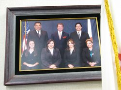 A portrait within a school board auditorium displays the current school board and superintendent.