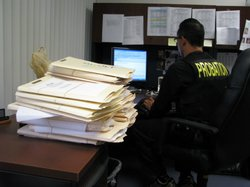 San Diego County Probation Officer Gonzalo Mendez works beside a stack of probation case files.
