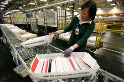 U.S.Postal worker Tin Aung moves boxes of letters and cards at the U.S. Post Office sort center December 15, 2008 in San Francisco, California.