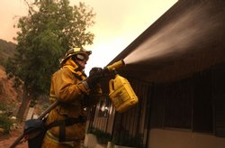 A Los Angeles City firefighter sprays foam fire retardant on a home September 1, 2009 in Tujunga, California. The out of control Station Fire has burned more than 120,000 acres, over 50 homes and has forced thousands of evacuations as nearly 10,000 homes are threatened.