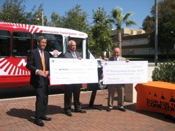 Randell Iwasaki (left), Director of Caltrans,  presents checks for new buses to Bob Campbell of North County Transit District (center) and Harry Mathis of the Metropolitan Transit System (right).