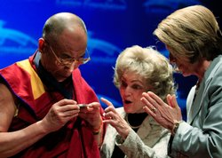 House Speaker Nancy Pelosi (D-CA) (R) presents the Dalai Lama (L) with the Lantos Human Rights Prize as Annette Lantos (C) looks on during a ceremony at the U.S. Capitol on October 6, 2009 in Washington, DC.