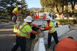 County workers add sand bags to concrete K-rails to divert mud flows around homes in advance of the first rain storm since before the massive Station fire began, on October 9, 2009 in La Canada Flintridge, California.