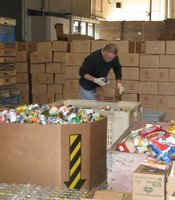 A volunteer does a rough sort of the donated food. He checks items and removes any that are dented or damaged.