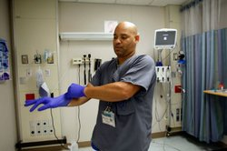 Miami VA Medical Center hospital registered nurse, Rafael Sepulveda, pulls on rubber gloves while attending to patients in the Emergency room in Miami, Florida. 