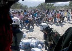 Haitian citizens receive water from air crewmen from Helicopter Sea Combat Squadron 9 assigned to the aircraft carrier USS Carl Vinson.