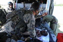 U.S. Air Force Tech Sgt. Nicholas Wentworth hangs an intravenous solution inside an MH-60S Sea Hawk prior to flying an earthquake victim to the aircraft carrier USS Carl Vinson.
