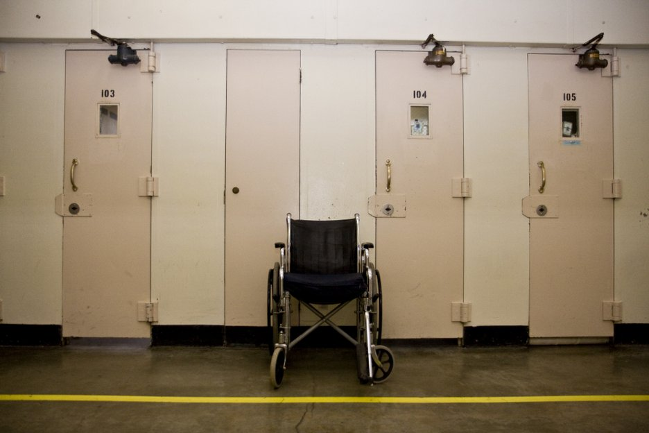 A wheelchair sits outside a prisoner's cell because the doors are  too narrow for it to fit inside.