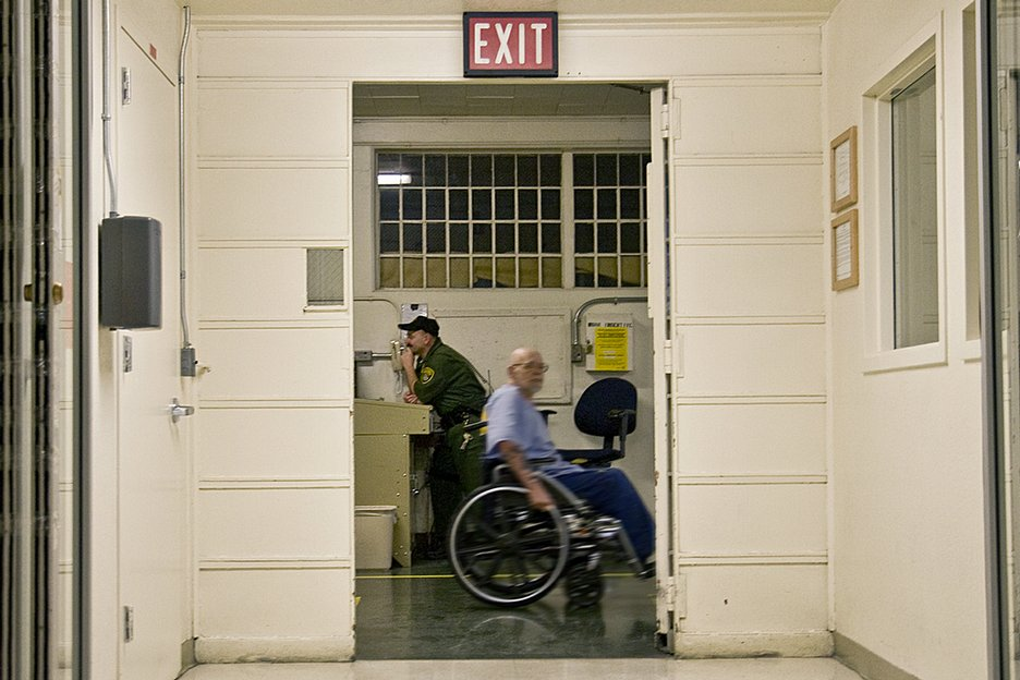 A prisoner in a wheelchair moves through the halls, a common sight  at the California Medical Facility at Vacaville.
