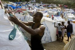 A man sets up a tent in a make-shift camp at a golf course on January 24, 2010 in Port-au-Prince, Haiti.