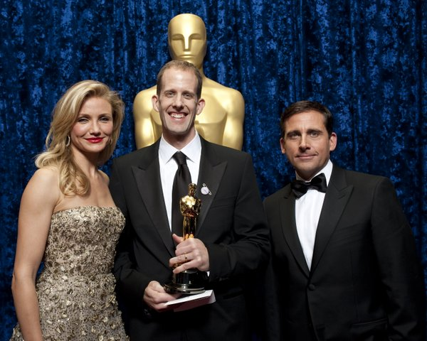 "Peter Docter, flanked by presenters Cameron Diaz and Steve Carrell, accepts the award for ""Up."""
