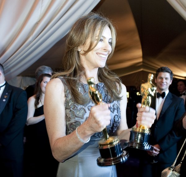 Kathryn Bigelow proudly holds her two Oscars for best director and best film.