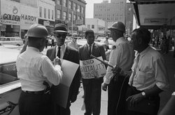 Roy Wilkins (left), executive secretary of the NAACP, and Medgar Evers (center), NAACP field secretary, are arrested for protesting beatings and arrests of civil rights demonstrators in Jackson, Mississippi. Evers was assassinated 10 days later.