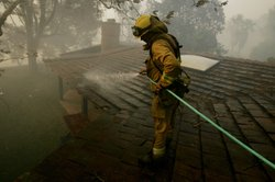 Firefighters Hollis Frands sprays down a rooftop to prevent it from catching on fire October 23, 2007 in Poway, California. The Witch Fire, which started outside of Ramona, California burned more than 1,000 structures and forced more than 300,00 to evacuate. (Editor's Note: KPBS initially posted a photo of the Harris Fire in this story, which is not at issue in this settlement. KPBS regrets the error.)