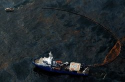 A boat uses a protective boom to collect oil on April 28, 2010 near New Orleans, Louisiana.
