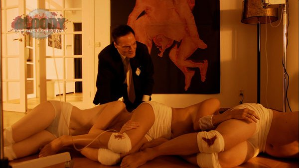"The mad doctor (Dieter Laser) and his creation in ""The Human Centipede"""